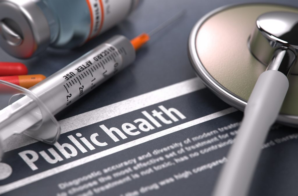 Public Health. Medical Concept with Blurred Text, Stethoscope, Pills and Syringe on Grey Background. Selective Focus.